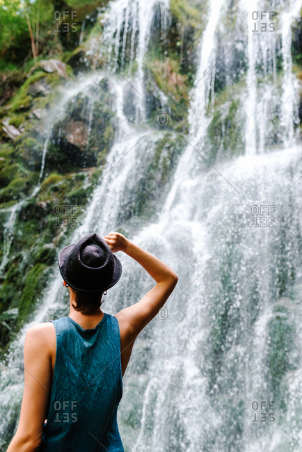 Low angle back view of androgynous female tourist standing on rock and enjoying amazing cascade waterfall during vacation
