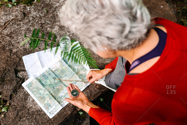 From above of anonymous female tourist orientating on map and compass while standing on rock in forest
