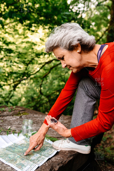 Side view of anonymous female tourist orientating on map and compass while standing on rock in forest