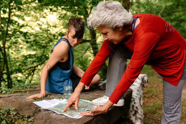 Side view of young and senior female travelers sitting on stone in woods and discussing location while orientating on map and compass