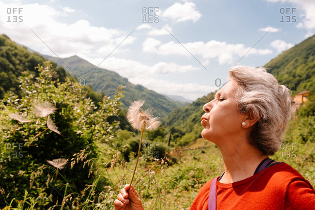 Side view of carefree female traveler blowing fluffy dandelion flower while standing in mountainous area on sunny day