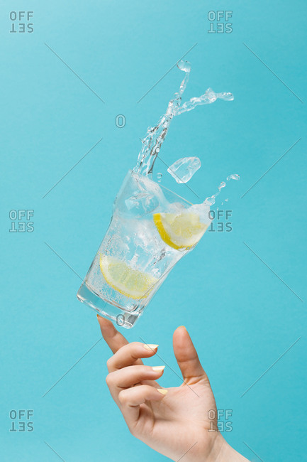 Unrecognizable female tossing glass of fresh water with ice and lemon on light blue background showing concept of diet