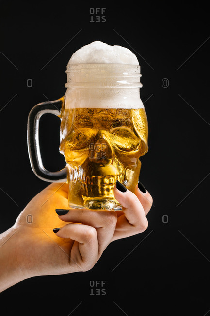 Crop female with glass in shape of skull filled with fresh beer with foam on black background in studio