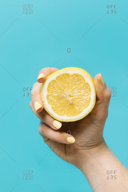 Anonymous female with yellow manicure showing half of ripe lemon on light blue background