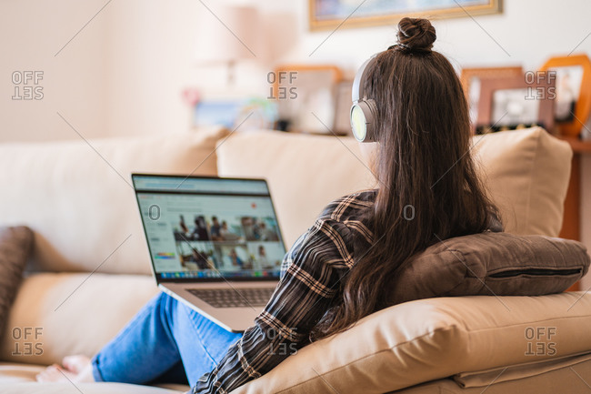 Young female student in casual wear with headphones watching video lesson on laptop while sitting on sofa in modern apartment