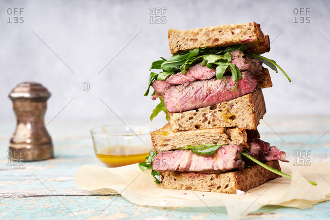 Close up of a pile of beef steak sandwich with arugula and mustard dressing against bright background