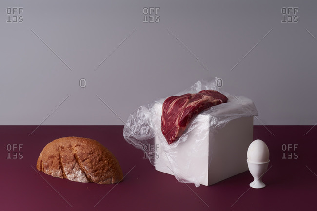 Still life with beef steak, an egg and a bread slice.