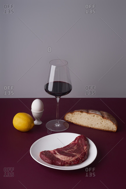 Still life with a glass of wine, beef steak and bread slice.