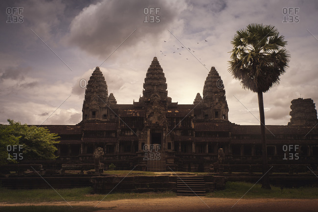 Stone oriental temple with shabby facade and towers on background of majestic sunset sky in Cambodia