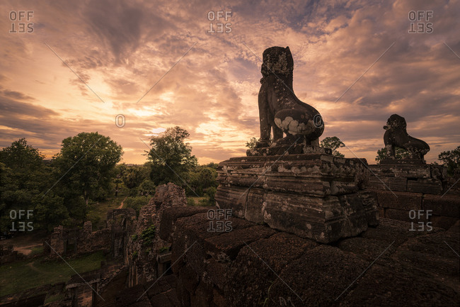 Spectacular scenery of traditional Buddhist temple with monuments of animals on background of magnificent sundown in Cambodia