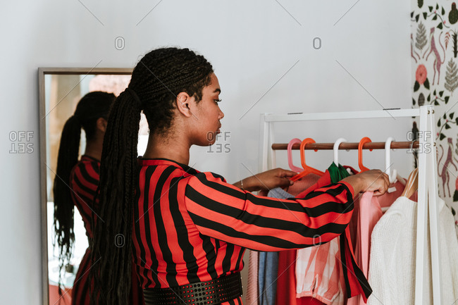 Trendy African American female with braids in striped dress holding high heels and hanger with shirt picking clothes at home