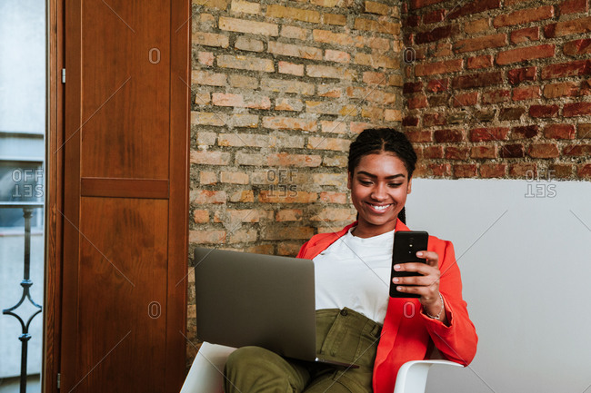 Happy elegant African American woman checking message on mobile phone while sitting with laptop in armchair against brick wall in loft apartment