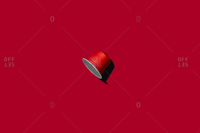 Top view of red coffee pod placed on red background
