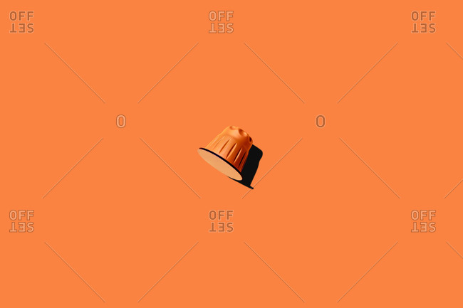 Top view of orange coffee pod placed on orange background