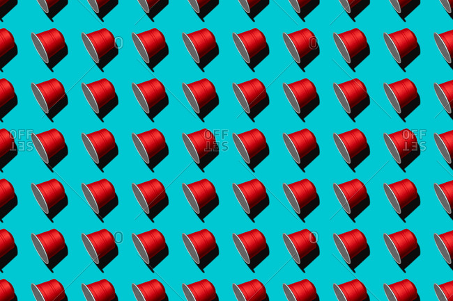 Top view of red coffee pods placed in even rows as seamless pattern on blue background