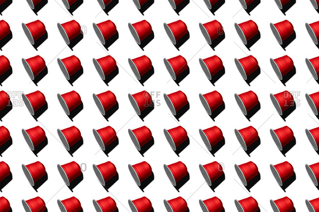 Top view of red coffee pods placed in even rows as seamless pattern on white background