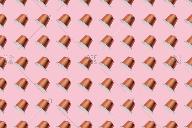 Top view of golden coffee pods placed in even rows as seamless pattern on pink background