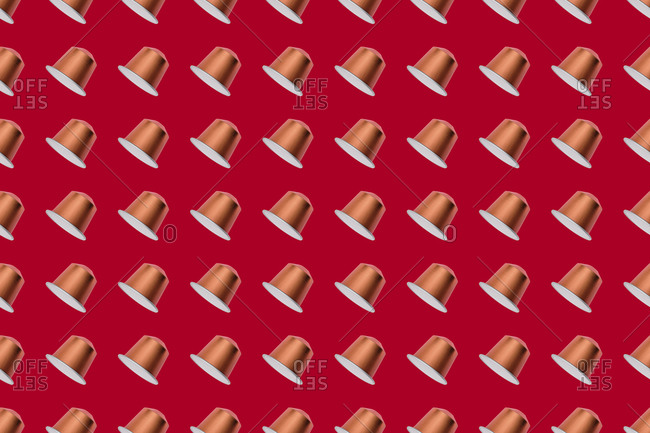 Top view of golden coffee pods placed in even rows as seamless pattern on red background