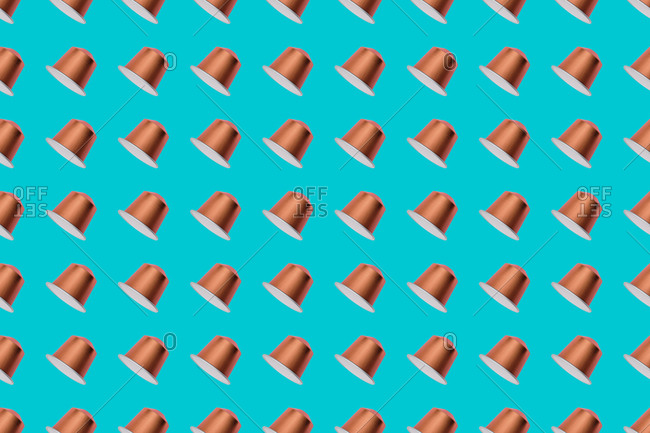 Top view of golden coffee pods placed in even rows as seamless pattern on blue background