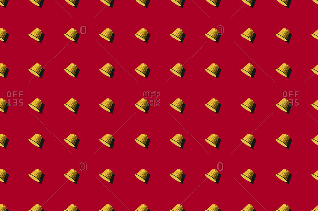 Top view of yellow coffee pods placed in even rows as seamless pattern on red background