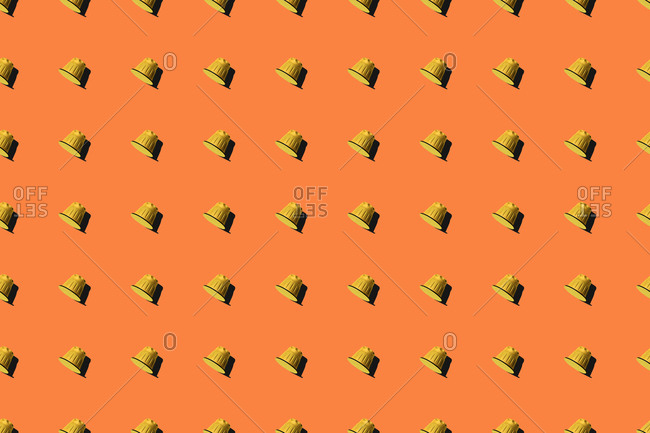 Top view of yellow coffee pods placed in even rows as seamless pattern on orange background