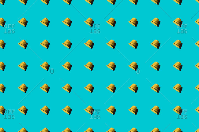 Top view of yellow coffee pods placed in even rows as seamless pattern on blue background