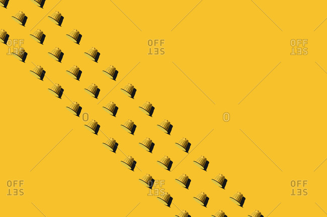 Top view of yellow coffee pods placed in even rows as seamless pattern on yellow background