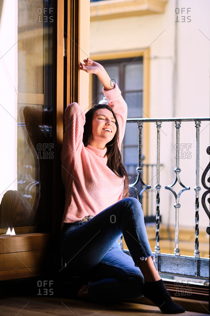 Carefree female in casual clothes sitting on floor near metal railing and tenderly stretching arms while enjoying morning at home
