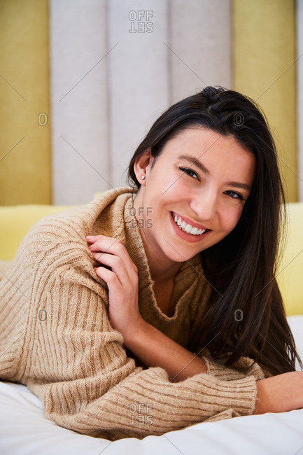 Charming female in oversize sweater and stockings lying on soft bed in modern bedroom and cheerfully looking at camera