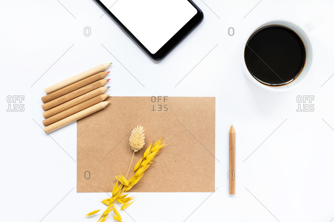 Top view of sheet of craft paper with dried spikelet and colored pencils arranged on white table with cellphone and cup of fresh coffee