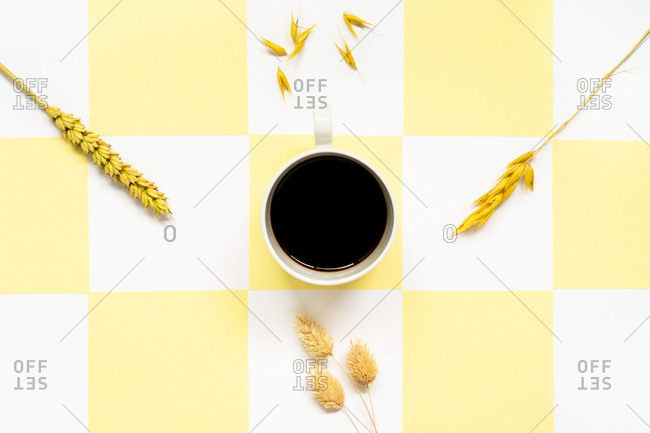 From above of mug with hot black coffee in center and different golden spiky cereal spikes on thin stalks aside