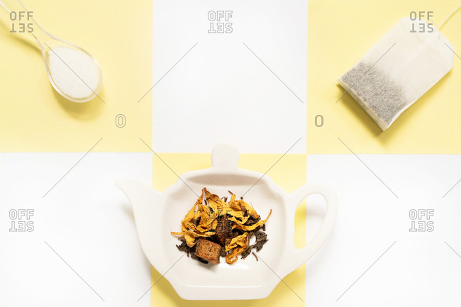 From above of ceramic plate in form of teapot with different dry spices near tea bag