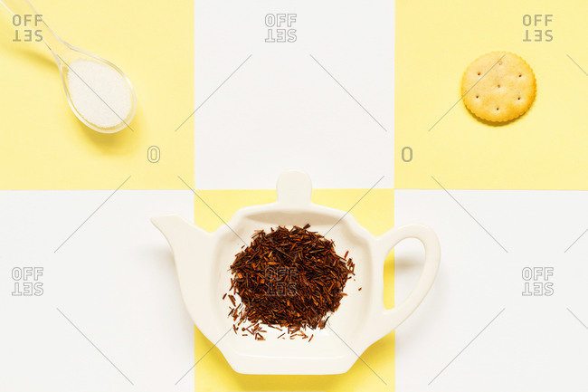 From above of ceramic plate in form of teapot with different dry spices near salty cracker