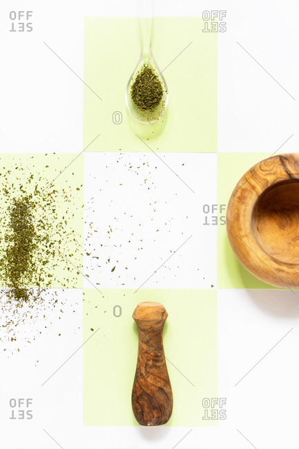 Top view of wooden mortar with pounder near spilled pepper and spiky dry anise with thin golden oat spike