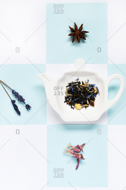From above of ceramic plate in form of teapot with different dry spices