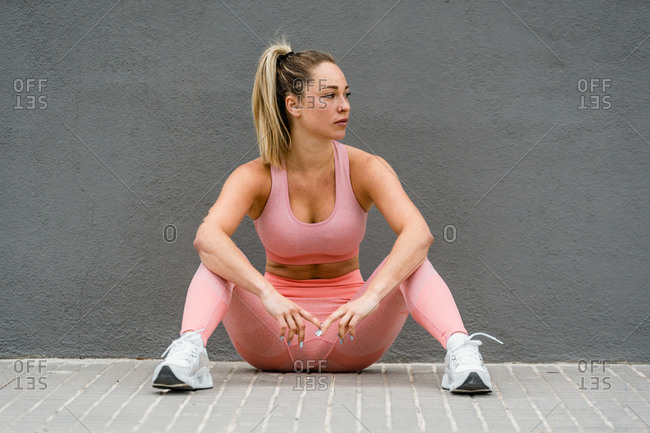 Full body of fit female athlete in sports wear and sneakers sitting near grey wall and looking away