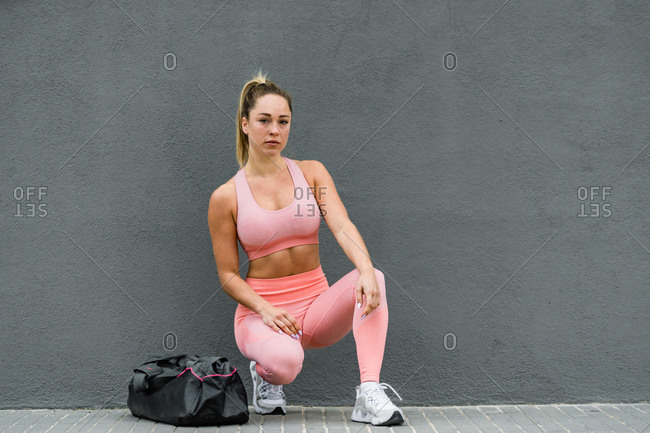 Slim blond female athlete in active wear and sneakers with sports bag strolling on embankment near grey wall in daylight