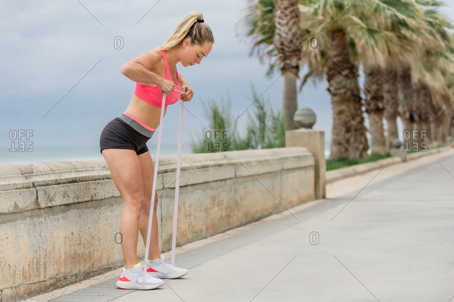 Side view of concentrated female athlete in sportswear practicing fitness with elastic tape while standing leaned forward on embankment near palms and sea under cloudy sky