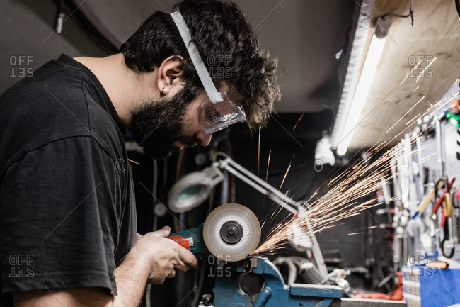 Side view of bearded male master wearing protective glasses standing in shabby workshop and cutting metal detail with grinder tool