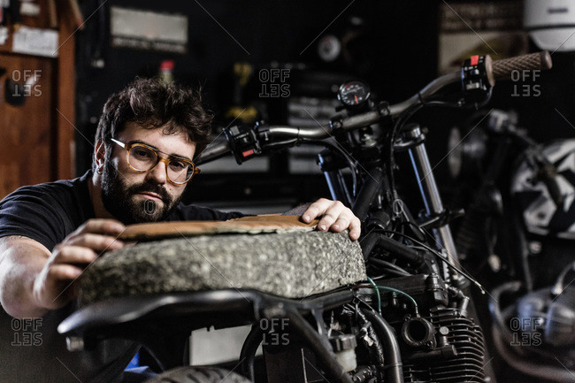 Tattooed male biker standing in shabby garage and measuring length of seat while fixing motorbike