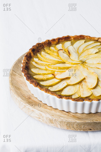 From above yummy freshly baked apple pie in casserole dish decorated with green apple slices and placed on table with white cloth