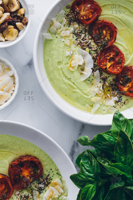 From above bowls with delicious avocado and apple cream soup decorated with sun dried tomatoes and toasted grated coconut with cashew nuts and fresh basil