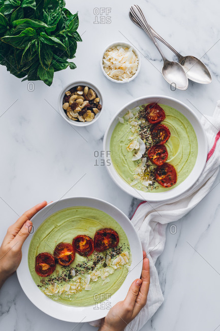From above of crop unrecognizable person serving bowls with delicious avocado and apple cream soup decorated with sun dried tomatoes and toasted grated coconut with cashew nuts and fresh basil