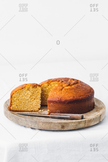 Delicious sweet sliced sponge cake placed with knife on wooden board against white background