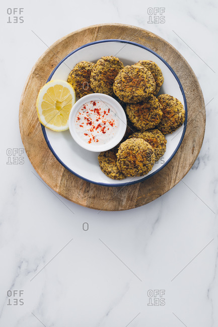 Top view of dish full of lentil falafel served with yogurt sauce on a wooden table