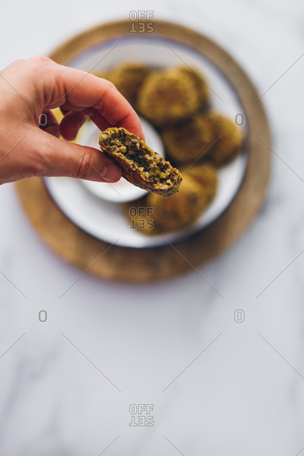 Top view of hand grabbing a lentil falafel from a dish served with yogurt sauce on a wooden table