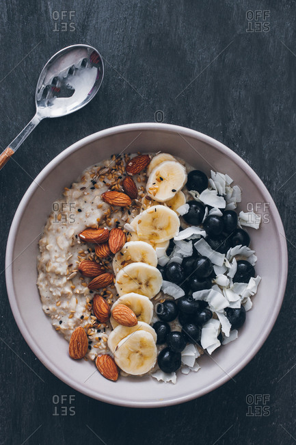 Top view of bowl of porridge with raw almonds, sliced banana, blueberries and grated coconut