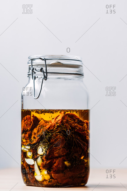 Side view of mixture of ingredients inside a glass jar ready to be used to prepare a red pesto recipe, neutral background