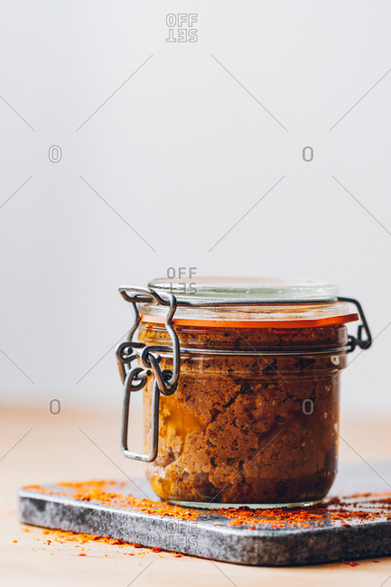 Side view of red pesto inside a glass jar against a neutral background