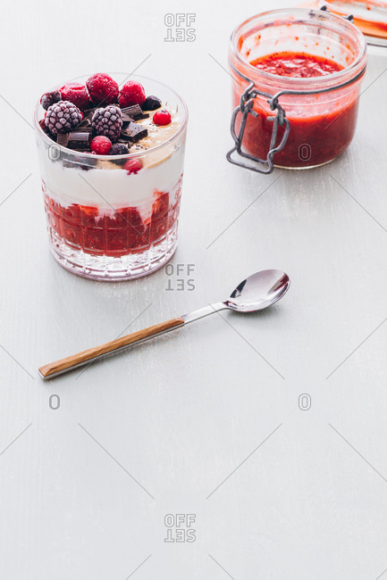 Glass of ice cream with strawberry jam, frozen berries and chocolate chips placed on a wooden white table